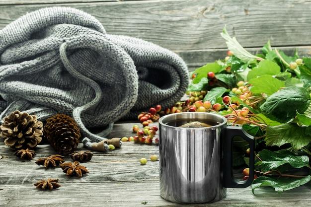 A xícara de chá em uma bela parede de madeira com suéter de inverno, frutas vermelhas, outono Foto gratuita