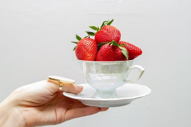 A xícara de chá está cheia de morangos na mão da menina. Foto Premium