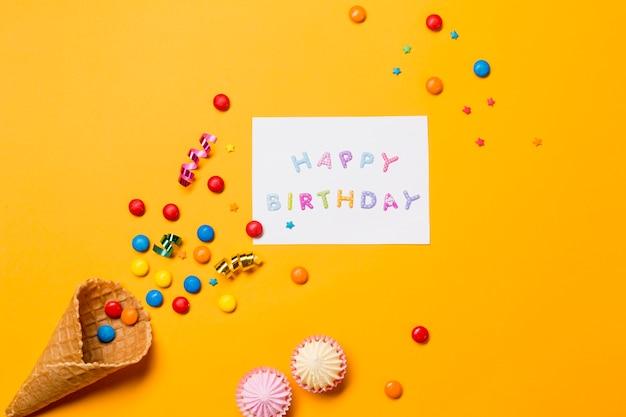 Aalaw; gemas e serpentinas do cone perto da mensagem de feliz aniversário em fundo amarelo Foto gratuita
