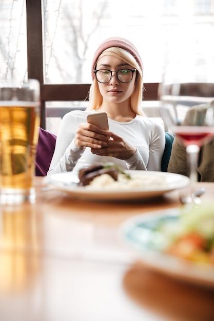 Aattractive mulher sentada no café enquanto estiver usando telefone celular Foto gratuita