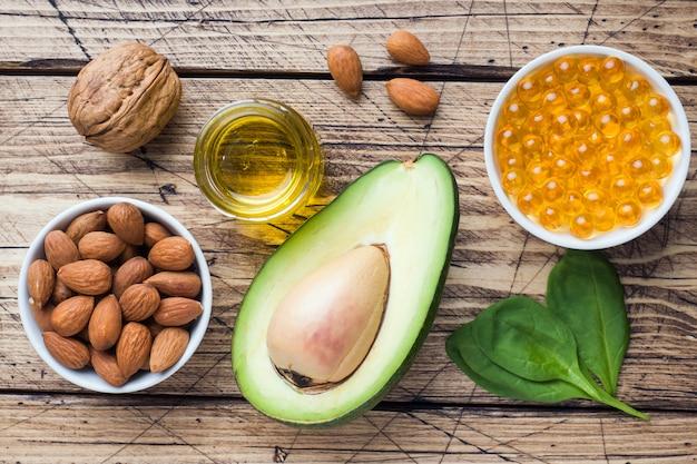 Abacate dos produtos do antioxidant do alimento saudável do conceito, porcas e óleo de peixes, toranja no fundo de madeira. Foto Premium