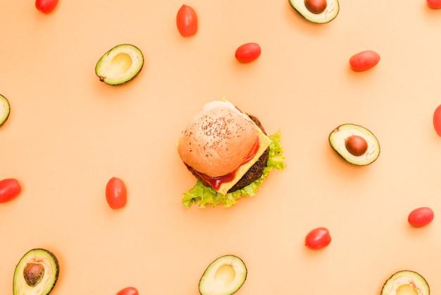 Abacate e tomate cereja rodeado em torno do hambúrguer em pano de fundo colorido Foto gratuita