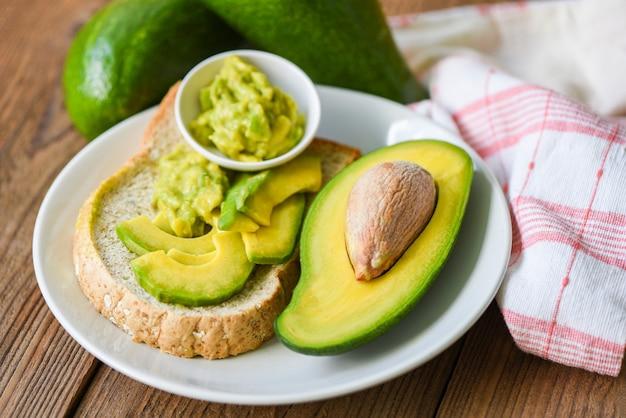 Abacate fatiado metade e molho de abacate amassado no prato branco Foto Premium