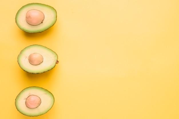 Abacate halved no contexto amarelo Foto gratuita