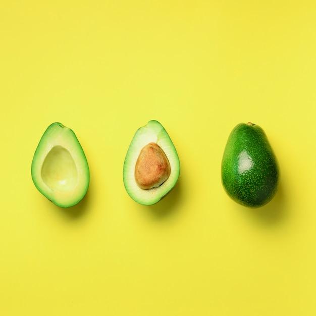 Abacate orgânico com semente, metades do abacate e frutos inteiros no fundo amarelo. teste padrão verde dos abacates no estilo mínimo da configuração do plano. Foto Premium