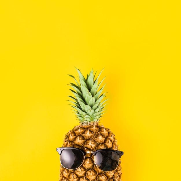 Abacaxi brilhante em óculos de sol Foto gratuita