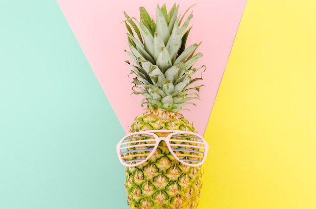 Abacaxi com óculos de sol na mesa Foto gratuita