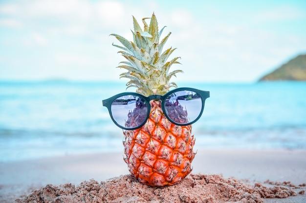 Abacaxi e óculos de sol na praia st mar verão Foto Premium