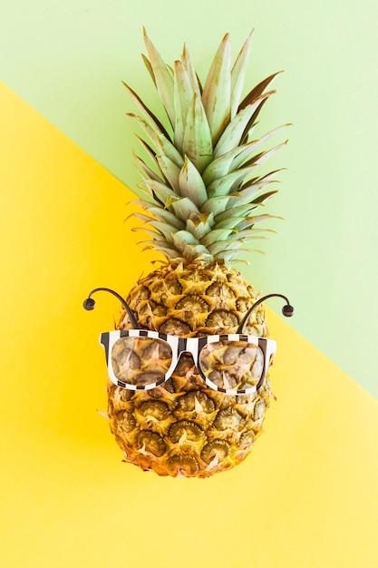 Abacaxi em óculos de sol em plano de fundo multicolorido Foto gratuita