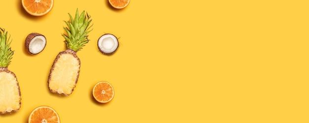 Abacaxi, limões, laranjas e cocos em um fundo amarelo. Foto Premium