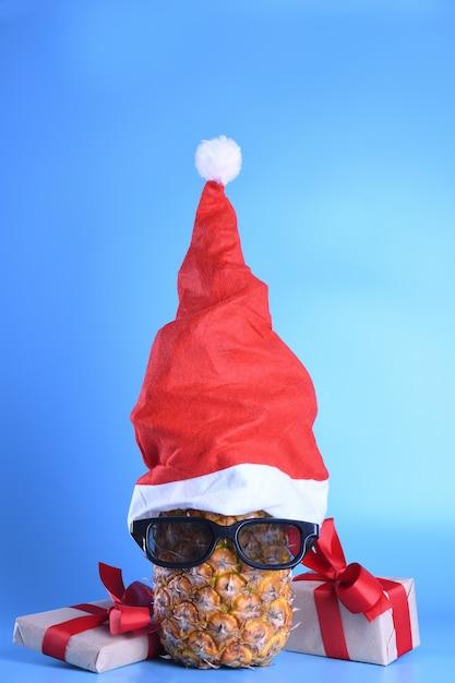 Abacaxi maduro, ananás com óculos de sol no chapéu de papai noel. ano novo conceito de fruta Foto Premium