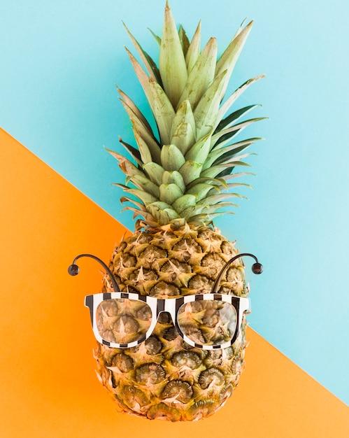 Abacaxi na moda em óculos de sol em plano de fundo multicolorido Foto gratuita