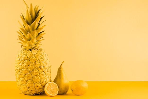 Abacaxi; pêra e limão ao meio em fundo amarelo Foto gratuita