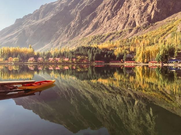 Abaixe o lago kachura no outono, no barco entrado e na reflexão da montanha na água imóvel. Foto Premium