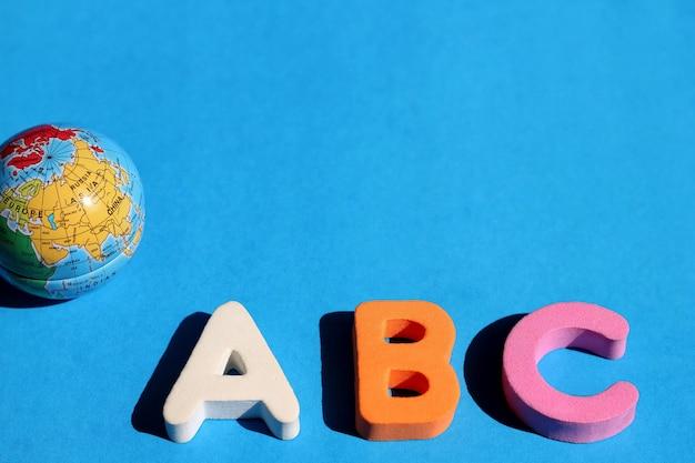 Abc primeira letra do alfabeto inglês e pequeno globo no azul Foto Premium