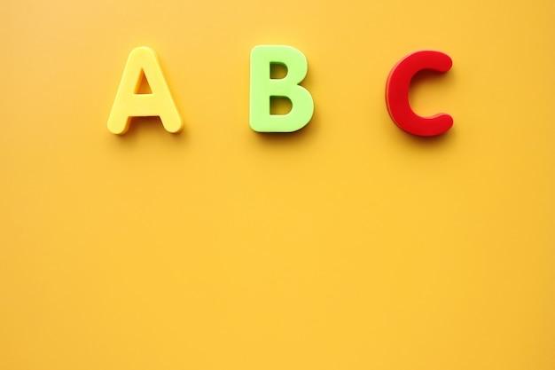 Abc primeiras letras do alfabeto inglês em um fundo amarelo. copie o espaço. Foto Premium