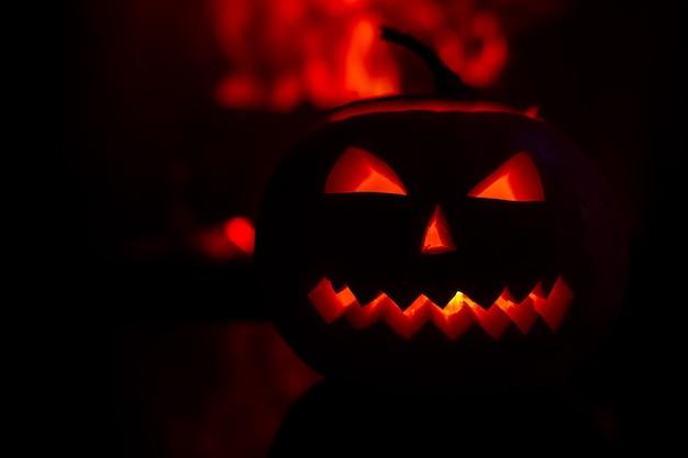 Abóbora assustadora para a celebração do halloween no fundo das chamas. Foto Premium