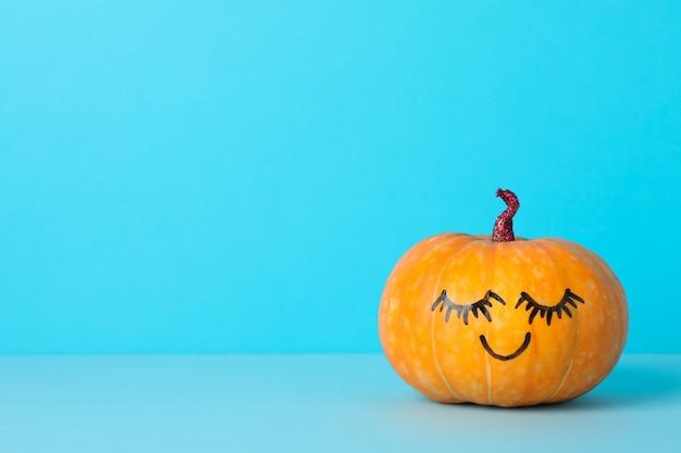 Abóbora com sorriso no azul, espaço para texto Foto Premium