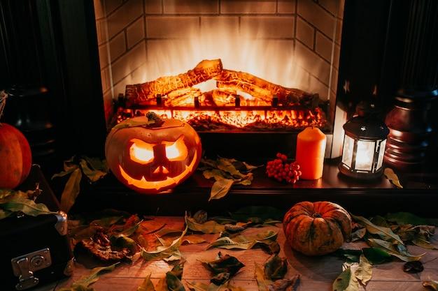 Abóbora de halloween assustador perto de uma lareira. fogo e folhas secas no fundo. jack da lanterna, copyspace. atire no escuro. Foto Premium