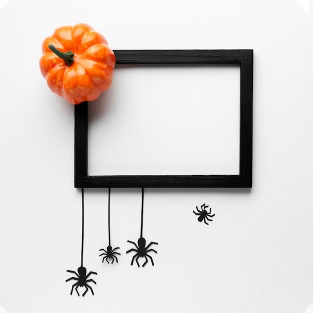 Abóbora de halloween e aranhas com moldura de mock-up Foto gratuita