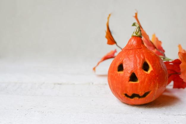 Abóbora de halloween e folhas de outono em fundo branco Foto Premium