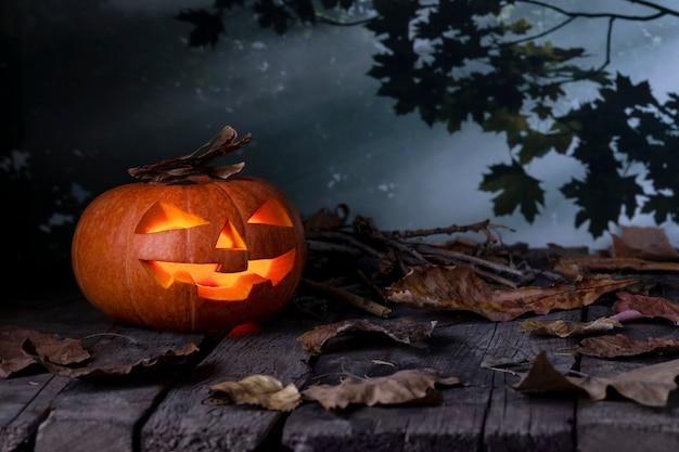 Abóbora de halloween jack o lantern brilhando em uma floresta mística à noite. Foto Premium