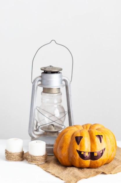 Abóbora de rosto assustador, velas e lanterna em uma mesa de madeira branca Foto Premium