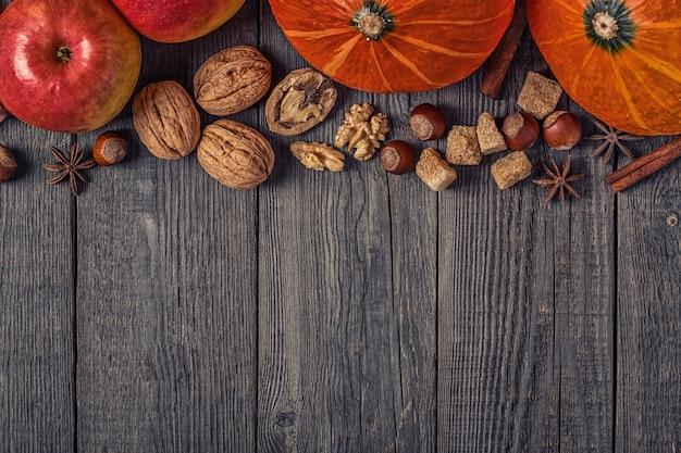 Abóbora e maçãs com nozes em uma mesa de madeira Foto Premium