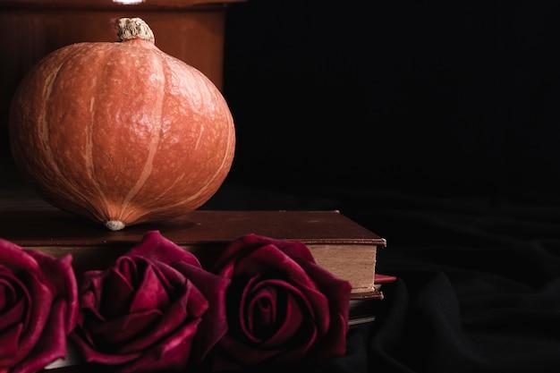 Abóbora e rosas em fundo preto Foto gratuita