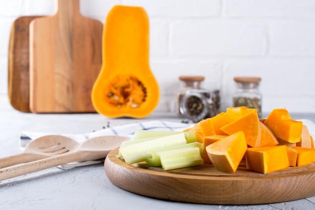 Abóbora fatiada em uma placa de madeira. comida caseira com abóbora. ainda vida na cozinha Foto Premium