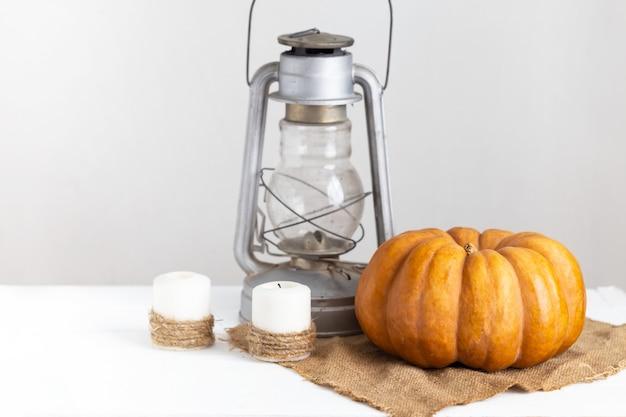 Abóbora, velas e lanterna em uma mesa de madeira branca. Foto Premium