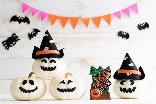 Abóboras brancas do fantasma com o chapéu da bruxa no fundo branco da placa de madeira com bastão. Foto Premium
