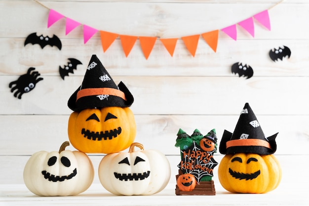 Abóboras brancas e amarelas do fantasma com o chapéu da bruxa no fundo branco da placa de madeira com bastão. Foto Premium