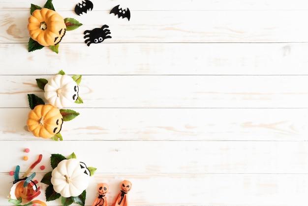 Abóboras de fantasma branco e amarelo com artesanato de halloween em fundo branco de madeira Foto Premium