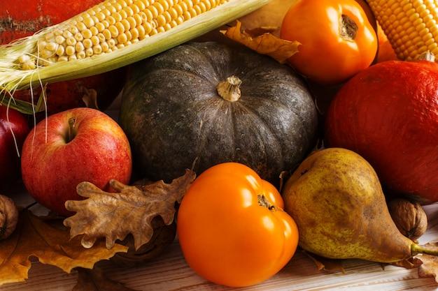 Abóboras de vegetais diferentes, maçãs, peras, nozes, milho, tomate, folhas secas de amarelas sobre fundo branco de madeira. colheita de outono, copyspace. Foto Premium