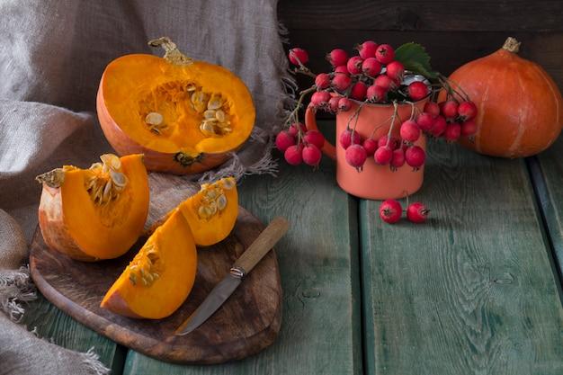 Abóboras e uma abóbora em uma placa de madeira no corte e uma faca, na caneca laranja encontra-se o hawthorn Foto Premium