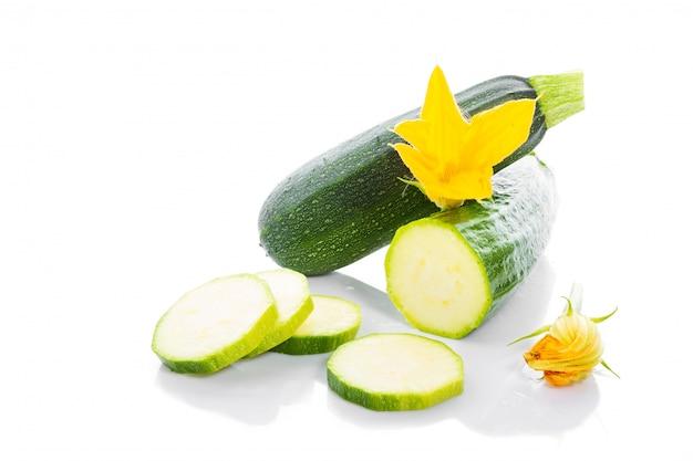 Abobrinha ou abóbora verde com folhas verdes e flores isoladas no branco Foto Premium