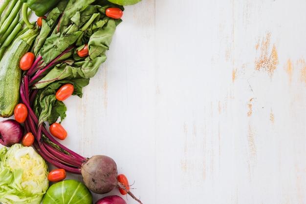 Abobrinha; tomates; repolho; cabaça e beterraba na mesa de madeira branca Foto gratuita