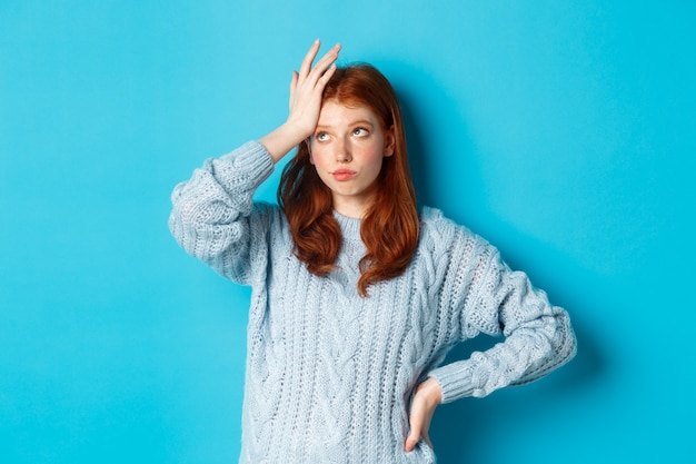 Aborrecida e cansada adolescente ruiva revirar os olhos, palma da mão e suspirando incomodada, parada em um suéter contra um fundo azul. Foto Premium