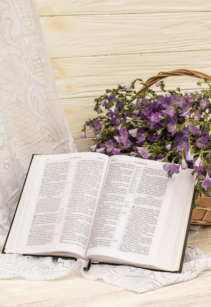 Abra a bíblia e o linho de buquê na cesta de vime. estilo retrô, vintage Foto Premium