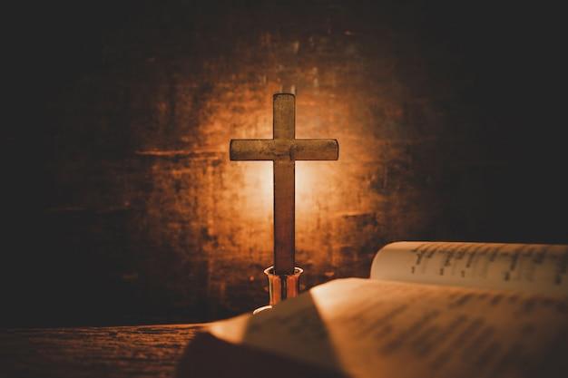 Abra a bíblia sagrada e vela em uma tabela de madeira velha do carvalho. belo fundo dourado. conceito de religião. Foto gratuita