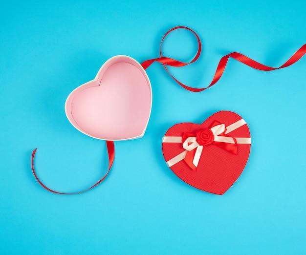 Abra a caixa de presente vermelha em forma de coração com um laço em um fundo azul Foto Premium