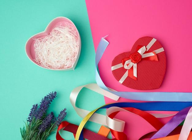 Abra a caixa de presente vermelha em forma de coração com um laço verde rosa Foto Premium