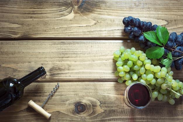Abra a garrafa do vinho tinto com wineglass, corkscrew e a uva madura na placa de madeira. Foto Premium