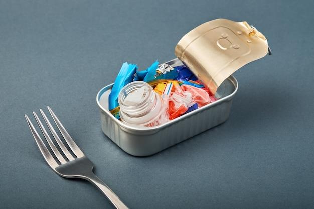 Abra a lata e o garfo. resíduos de plástico em vez de peixe dentro. conceito de poluição plástica do oceano Foto Premium