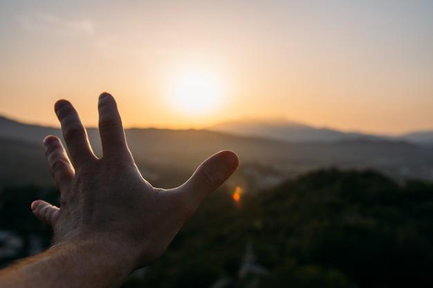 Abra a mão na direção do horizonte com um belo pôr do sol Foto Premium