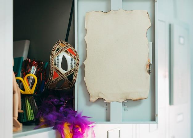 Abra a porta do armário com a página queimada; mascara de carnaval; tesoura e boa de penas Foto gratuita