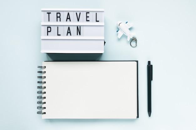Abra o bloco de notas, o avião, a caneta e o texto plano de viagem sobre fundo azul. viagem para fazer lista, férias e voos internacionais durante o conceito covid-19 do coronavírus. camada plana, cópia espaço, simulação Foto Premium