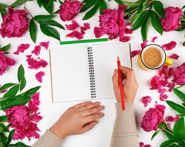 Abra o caderno em uma gaiola e duas mãos femininas, uma xícara amarela com café Foto Premium