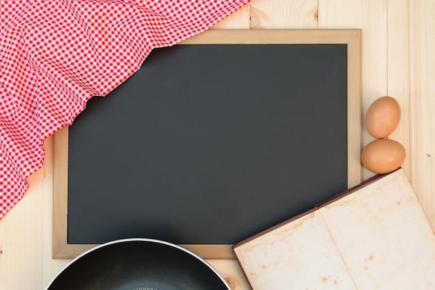 Abra o livro de receitas em um quadro negro com uma toalha de mesa quadriculada vermelha Foto Premium